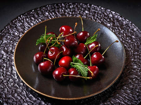 Ripe sweet cherry with mint leaves on brown plate Stock fotó