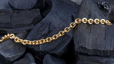 Golden chain on black coal background. Close up photo