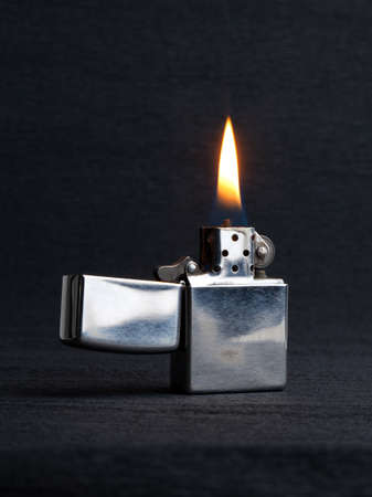 Close-up of metal gas lighter with burning fire on gray background with copy space