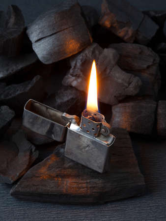 Close-up of metal gas lighter with burning fire on dark coal background with reflections