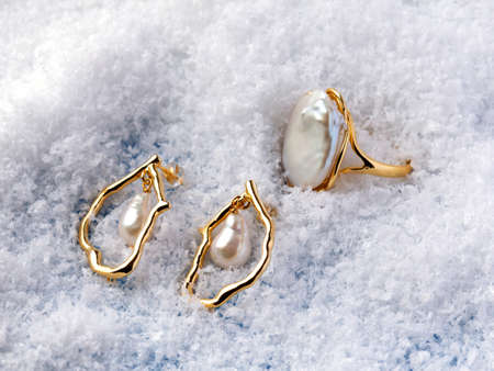 Luxury elegant baroque pearl ring and earrings on white snow background. Close-up shot