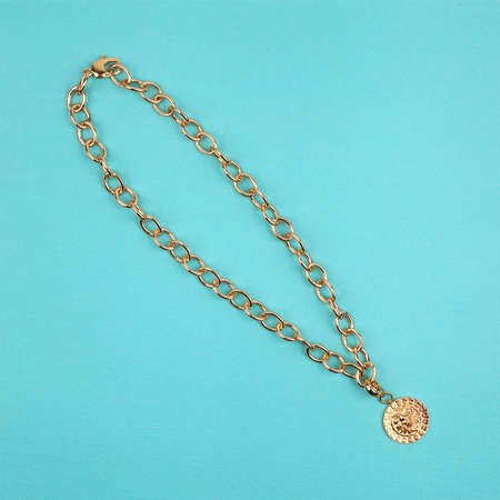Golden pendant with chain on bright turquoise background. Close-up shot