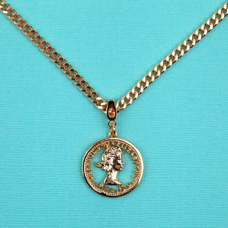 Female golden pendant with chain on bright turquoise textured background. Close-up shot