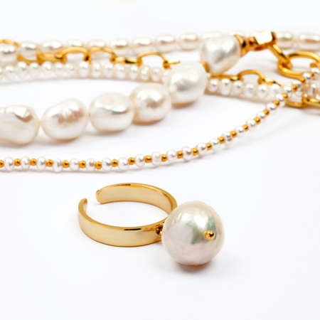 Luxury elegant baroque pearl ring with necklaces on white background. Close-up shot. Selective focus