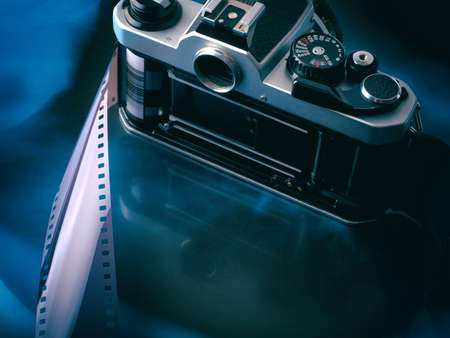 Open old vintage film camera with film strip on abstract gradient blue black background. With copy space