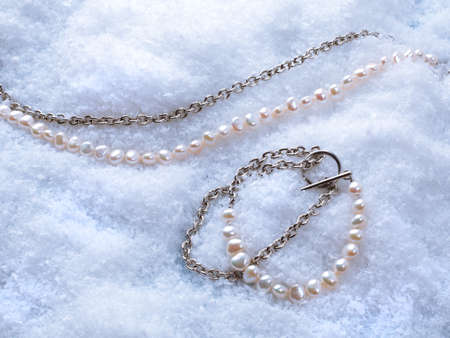 Luxury elegant gray baroque pearl bracelet and necklace on white snow background. Close-up shot