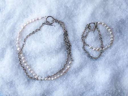 Luxury elegant baroque pearl bracelet and necklace on white snow background. Close-up shot
