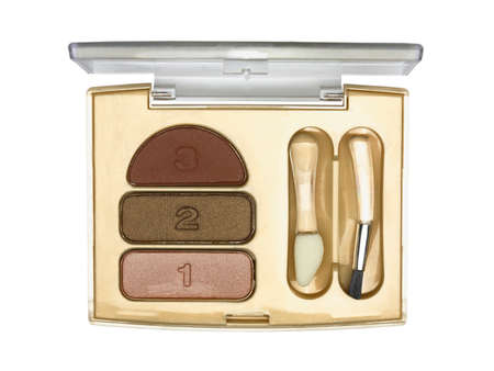 Open cosmetic set with eye shadows, brush and applicator in golden plastic case isolated on white background