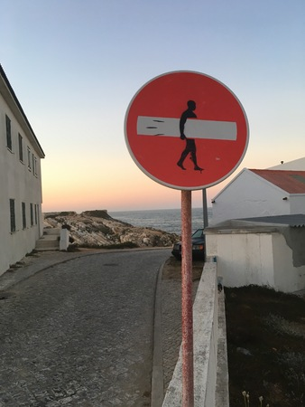 traffic sign turned into a surfboard with sunset