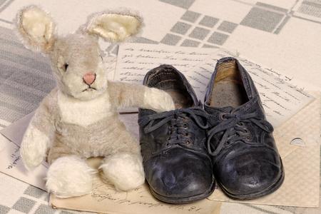 Erinnerung an Kindheit Konzept: Vintage Spielzeug Hase und Kinderschuhe Standard-Bild - 73747493