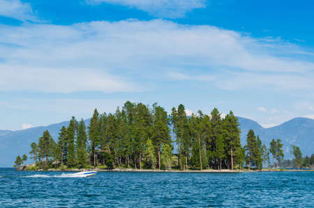 tree filled island in Flathead Lake, Montana with boat passing by and mountains in the distance