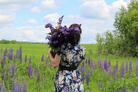 소녀는이 꽃밭 위에 그녀의 어깨에 lupines의 큰 꽃다발을 운반합니다. 사진은 뒤에서 찍은.
