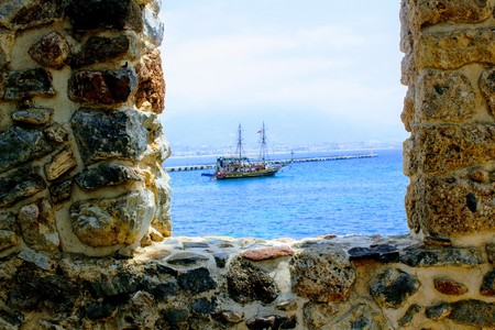 View of a pleasure sailing ship for a sea excursion through the loophole of the fortress wall (Antalya, Turkey).