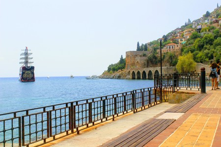 View from the embankment to the old shipyard Kızıl Kule and sea vessels (Antalya, Turkey).