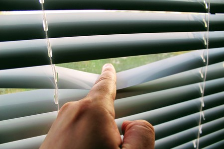 Male finger pushes white horizontal aluminum blinds.