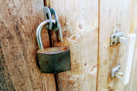 Open a padlock with traces of rust hanging on the door.