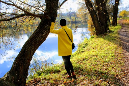 A woman in a yellow coat is standing on the shore of a pond in the estate of Count Leo Tolstoy in Yasnaya Polyana. Stock Photo