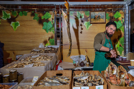 papakha: Moscow, Russia - February 25, 2017: Bearded seller of dried and smoked fish at the time of the break at work on fair