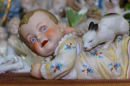 Moscú, Rusia - 19 de marzo de 2017: Colección de antigüedades estatuilla de porcelana Ruddy niño jugando con el conejo en la feria de antigüedades Editorial