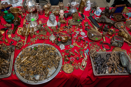 Moscow, Russia - March 19, 2017: Bronze, brass handmade souvenirs are spread out on the table mixed with antiques