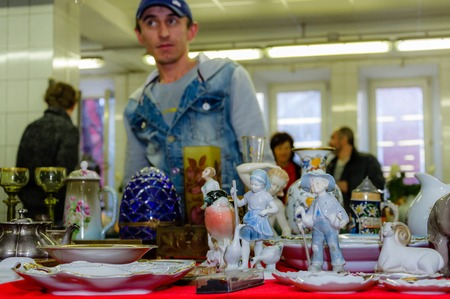 Moscow, Russia - March 19, 2017: Old antique porcelain and ceramic figures for sale on the flea market. Selective focus Редакционное