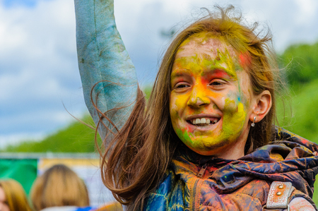 Moscow, Russia - June 3, 2017: Girl child sincerely enjoys what is happening at the summer Holi color festival