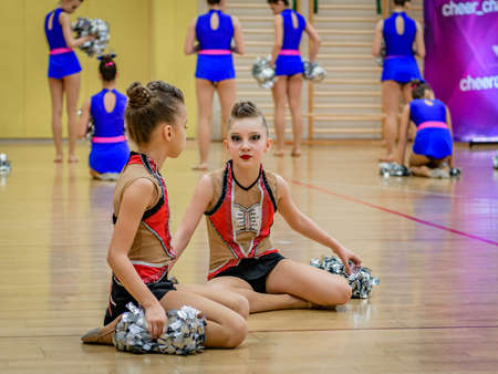 Moscow, Russia - December 22, 2019: Little girls cheerleader athletes rest between performances sitting on floor in gym, heerleading is popular among kids and adolescents they participate in shows