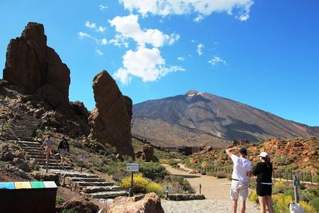 Tourists look at the volcano Фото со стока