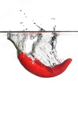 red chilli pepper plant: Red hot chili splashing into water on isolated white background Stock Photo