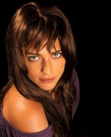 Beautiful brunette woman looking on black background photo
