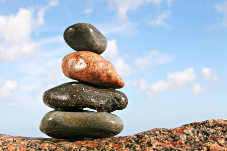 Stack of four balanced stones on a big rock with blue sky photo