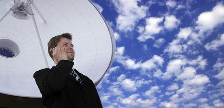 industrie: Erfolgreicher Geschäftsmann mit Handy vor riesiger Satellitenschüssel Stock Photo