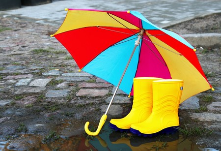 umbrella rain: Pair of yellow rubber boots with an open umbrella beside a puddle