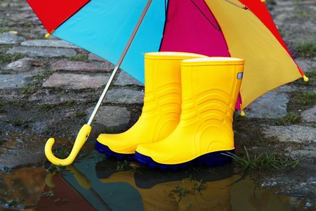 Pair of yellow rubber boots with an open umbrella beside a puddle   photo
