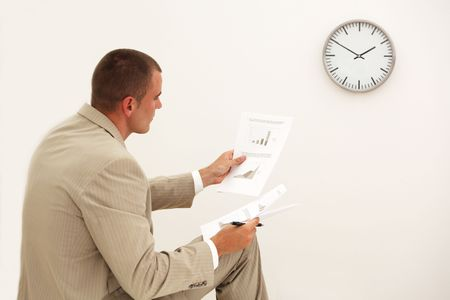 Businessman looking at documents with a clock showing 5 to 12 in the background Stock Photo - 5361328