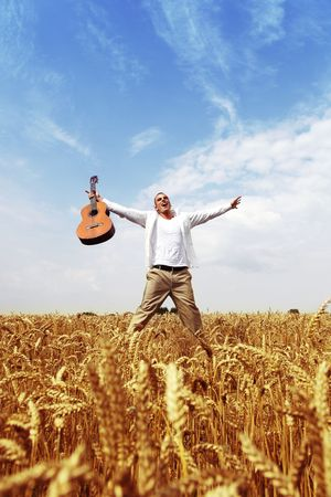 Happy man jumping in a wheat field with his guitar