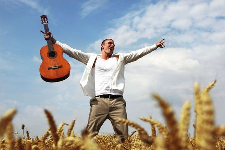 picknic: Happy man jumping in a wheat field with his guitar