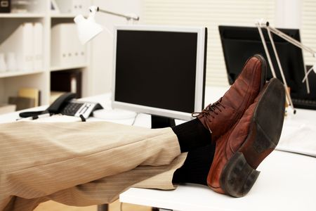 Feet of a businessman on the table in his office photo