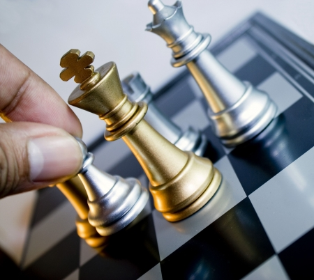pawn: Hang fingger move silver chess pawn next to gold king and silver queen. In the back there is silver rook.  Stock Photo