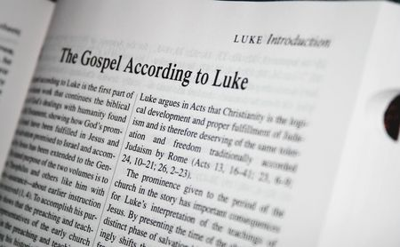 Bible gospel according to luke. White pape, black background. Taken from catholic bible study.