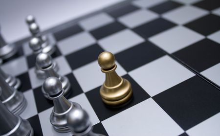 troop: Gold chess pawn in front of white troop. Black and white chess board.