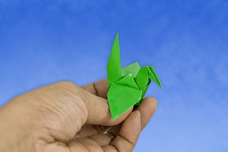 crane origami: Bird crane origami in the blue sky with hand, fliying at the blue sky.
