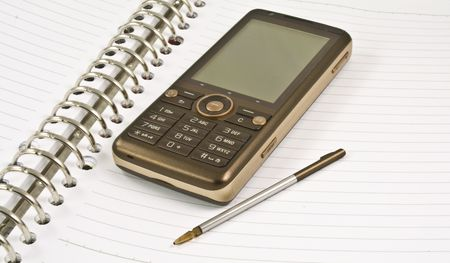 Blank white notebook with stylus ring on it and mobile phone ready to be written at book.