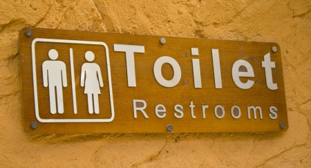 public restroom: Wooden toilet sign with orage background, and wood background. Stock Photo