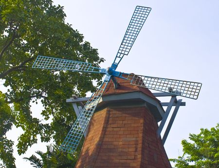Blue tradinional rustic windmill with blue sky and green tree as background.