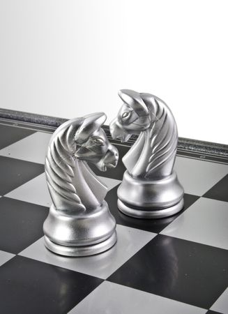 Two horses chess in the chess board ready to fight.