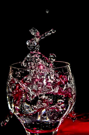 edge of the ice: Ice splashing into a glass with black background