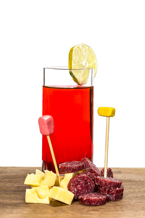 vermouth: glass of red vermouth with cheese and salami on a white background