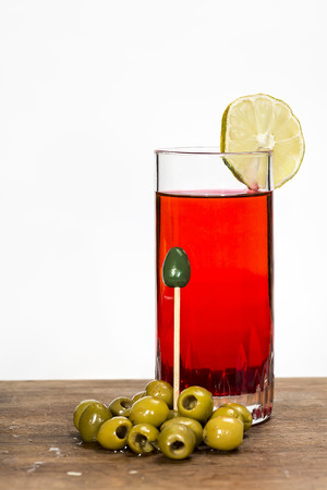 vermouth: glass of red vermouth with olives on a white background Stock Photo