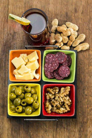 vermouth: glass of vermouth salami with cheese olives nuts and peanuts on a wood table